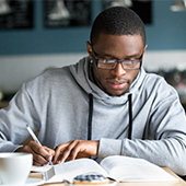 Young man with open book, studying and taking notes.