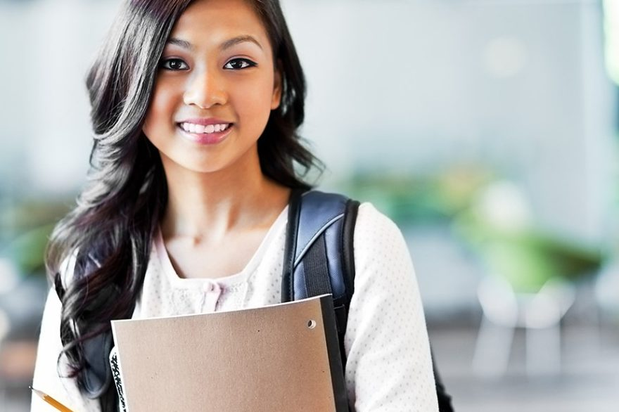 Young, college-aged woman holding notebook and backpack