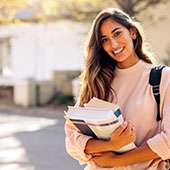 College student standing and smiling holding a stack of books